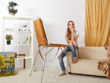 Painter woman with wooden sketchbook sitting on sofa and painting