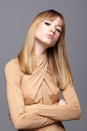 Portrait of blonde young woman with hands crossed. Female with green eyes and long straight hair. Girl dressed in beige dress on gray background.