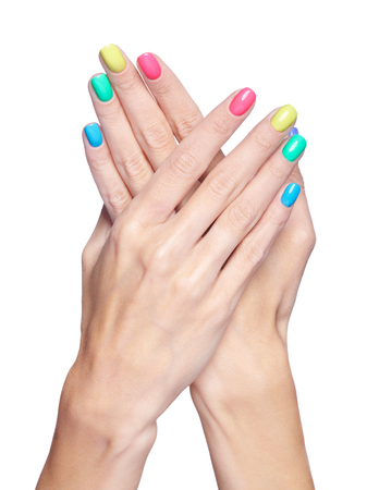 Female fingers with fancy bright green, yellow, pink and blue nails manicure. Girls hands isolated on white background