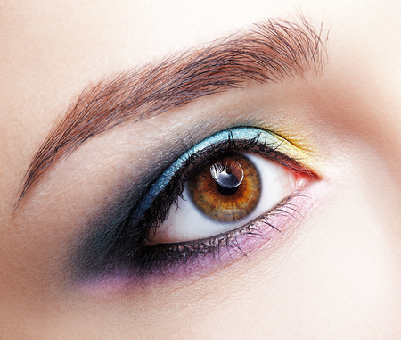 Closeup macro shot of  human female eye. Woman with natural evening vogue face beauty makeup. Girl with perfect skin and lilac - blue - yellow eyes shadows
