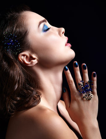 Portrait of beautiful brunette woman on black background. Female with blue eye shadow make up and manicure Stock Photo