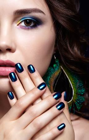 Portrait of beautiful brunette woman on black background. Female with blue eye shadow make up and manicure. Girl with peacock feather earrings