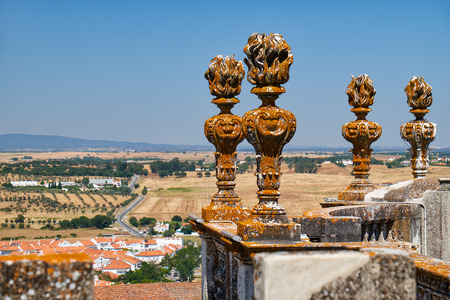 decorative balcony: The view of decorative stone torches on the balcony of Evora Cathedral (Se) with the residential city houses and fields on the background. Evora. Portugal