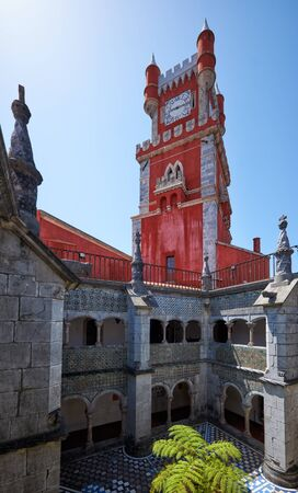 The view of the Red Clock tower and the Manueline Cloisters as seen from the inner yard of the original Monastery of the Hieronymite monks. Pena Palace. Sintra. Portugal