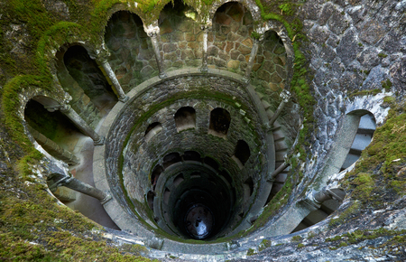 The view inside Initiation Well, whose mossy wells resemble underground towers lined with stone stairs. It was served for ceremonial purposes of initiation rites. Quinta da Regaleira. Sintra. Portugal Редакционное