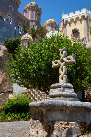 The view of the Pena Palace courtyard with the twisted stone cross on the foreground. Sintra. Portugal