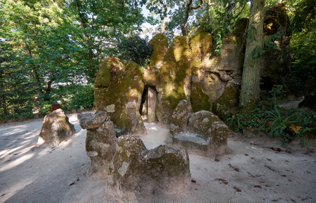 The upper entrance to the Initiation Well (Inverted tower) hided behind the mossy stones and vegetation in the park of Quinta da Regaleira estate. Sintra. Portugal 写真素材