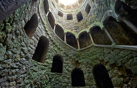 A staircase descending in a spiral along the walls of Initiation Well (Inverted tower) in Quinta da Regaleira estate. Sintra. Portugal