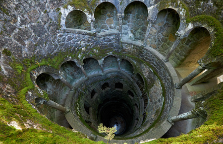 The view inside Initiation Well, whose mossy wells resemble underground towers lined with stone stairs. It was served for ceremonial purposes of initiation rites. Quinta da Regaleira. Sintra. Portugal Stock Photo