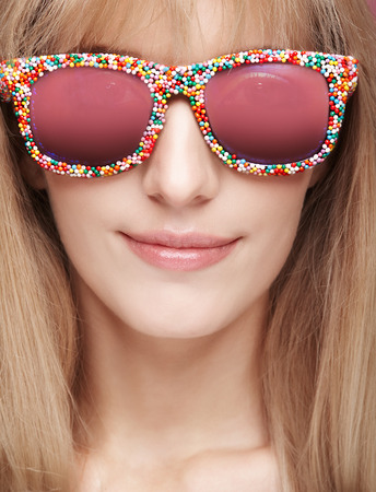 Closeup portrait of young blonde smiling woman with fun candy glasses