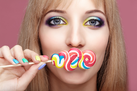Beauty portrait of young blonde woman on pink background. Female with candy lollipop on stick in hands. Girl has finger nails with bright yellow, green, blue and pink manicure.