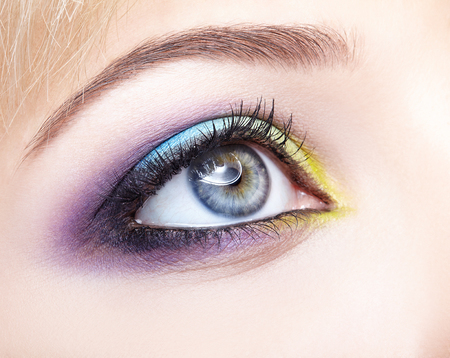 Closeup macro image of human female eye with violet shadows, blue and and yellow makeup