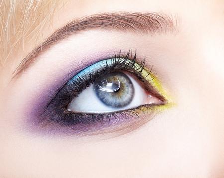 Imagen macro de primer plano del ojo femenino humano con maquillaje violeta sombras, azul y amarillo