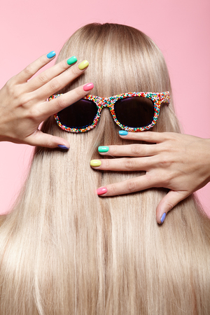Rear view of young woman. Blond stright hair with fun sunglasses.Female finger nails with bright manicure Stock Photo