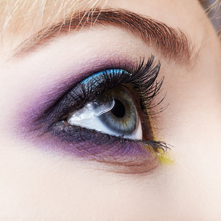 Closeup macro image of human female eye with violet shadows, blue and and yellow makeup Stock Photo