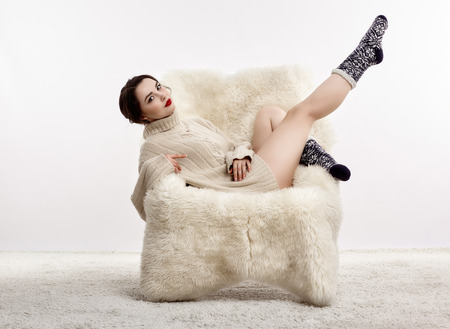 Portrait of beautiful brunette woman with leh up. Female is dressed in white cashmere sweater and woolen socks. Girl is sitting on white fur arm-chair  staying on furry carpet Stockfoto