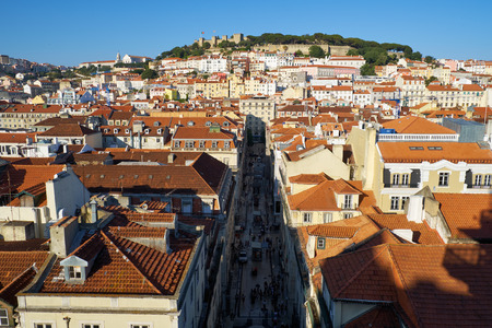 Residential houses of Alfama with Saint George Castle on the hill on the background and Santa Justa street on the foreground as seen from the observation platform of Santa Justa Lift. Lisbon. Portugal