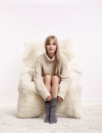 Portrait of beautiful blonde woman dressed in white cashmere sweater and woolen socks is sitting on white fur arm-chair staying on furry carpet