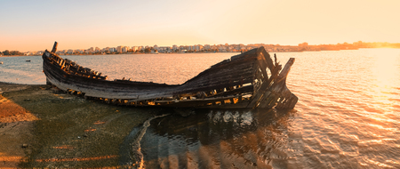 The panoramic view of the wrecks of the old wooden sailboat destroyed and burned on the bank of the Seixal Bay of Tagus river in the sunset light. Lisbon. Portugal