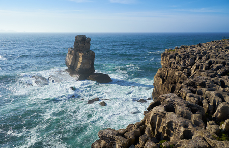 Rocks and waves of surf in the ocean near Cabo Carvoeiro (Cape of Coal), Peniche peninsula, Portugal