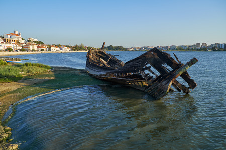 The view of the wrecks of the old wooden sailboat destroyed and burned on the bank of the Seixal Bay of Tagus river. Lisbon. Portugal