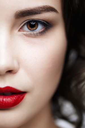 Closeup macro portrait of female face. Human woman half-face  with day beauty makeup. Girl with perfect skin.
