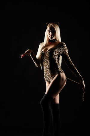 Blonde female dressed in cat girl suit. Woman in fancy masquerade costume of leopard.