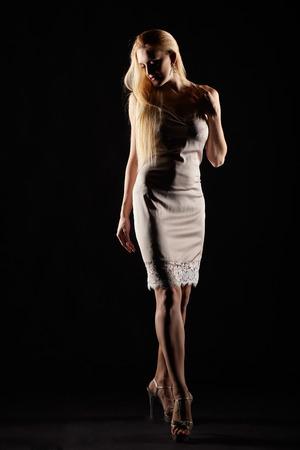 Blonde female dressed in night dress. Woman in nightie on black background. Imagens