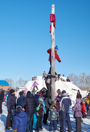 NOVOSIBIRSK, RUSSIA - JANUARY 11, 2018: Boy climbing on a wooden pole for the prize. Slavonic folk festivities Shrovetide or Maslenitsa. Historical and Architectural Museum in the open air