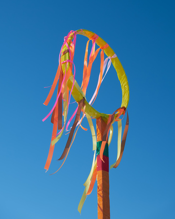 Wheel with ribbons on blue sky background. Slavonic folk festivities Shrovetide. In russian holiday Shrovetide is called Maslenitsa