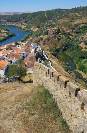 The defensive wall with battlements which encloses an area of the old town with the Guadiana river and the residential houses of Mertola on the background. Mertola. Baixo Alentejo. Portugal
