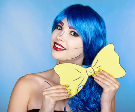 Portrait of young woman in comic pop art make-up style. Female in blue wig on blue background. Girl with yellow bow-tie in hands