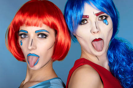 Portrait of young women in comic pop art make-up style. Females in red and blue wigs on blue background. Girls show each other tongues