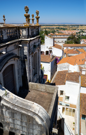 The view of balcony of the Evora Cathedral (Se) with stone torches and the nearby residential houses. Evora. Portugal