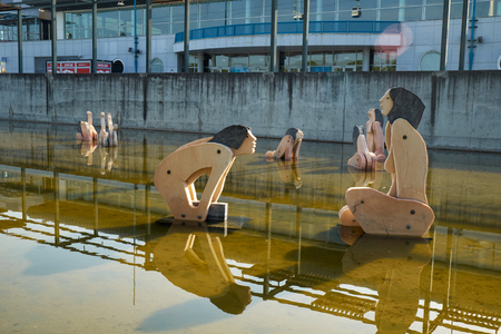 LISBON, PORTUGAL - JULY 04, 2016: The wooden figures of Tagides  - the nymphs of the Tejo river in the Lake Tagides in the Park of the Nations. Lisbon. Portugal