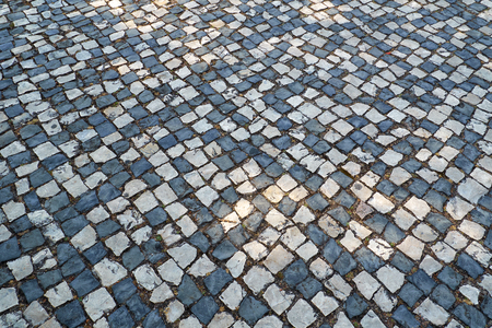 The pattern of tradition Portuguese pavement mosaic designed with black and white stones of basalt and limestone in the Park of the Nations. Lisbon. Portugal