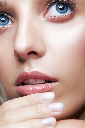 Closeup macro shot of female face and eyes beauty makeup. Woman with glossy glitter white skin. Girl with hand near face.