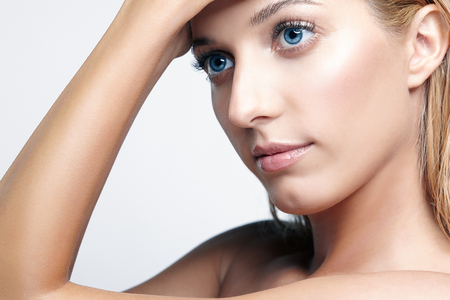Closeup  shot of female face and eyes beauty makeup. Woman with glossy glitter white skin. Girl with hand near face.