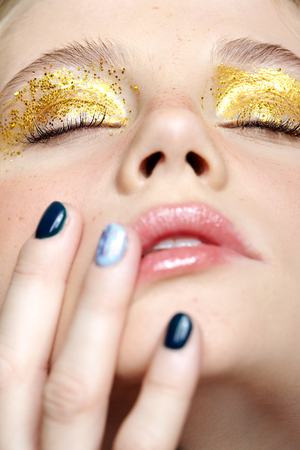 Closeup macro shot of human female face with closed eyes. Woman with unusual glitter glitzy vogue face beauty makeup. Girl with perfect skin and yellow smoky eyes eye shadows