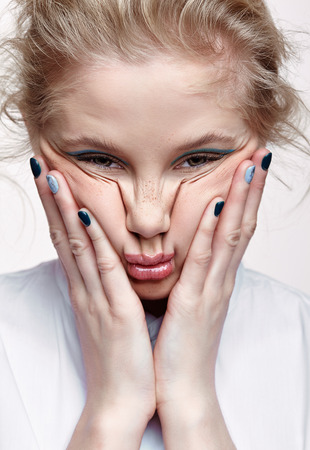 Emotional portrait of a young blonde woman on gray background. Female squeezes face skin on cheeks