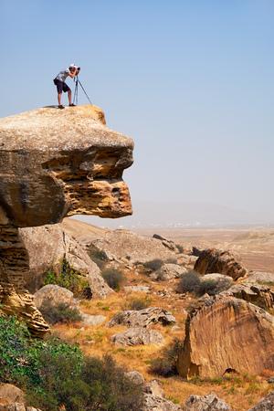 Photographer with tripod on the overhanging over plane rock cliff. Gobustan, Azerbaijan. Foto de archivo