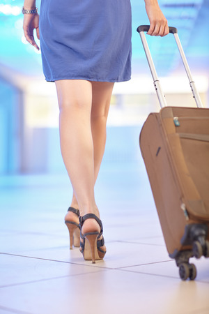 Young woman in blue dress and high-heels walks around the airport hall and carrying a suitcase on wheels. Vacation travel concept