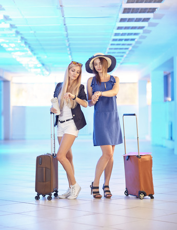Two young women with suitcases in the airport lounge