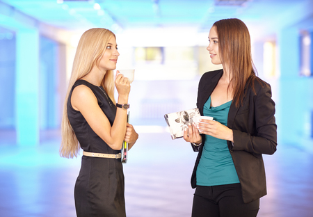 Two girls in the office with tablets and coffee cups in hand. Young women discuss office work. Blue empty hall on the background