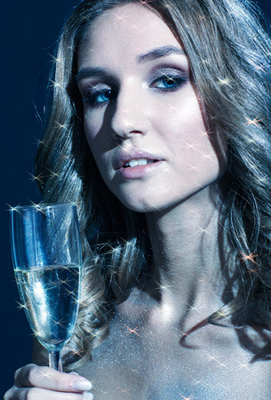 Girls with glass of champagne in hand. Beautiful young woman with vogue shining sparkle face makeup. Female Christmas portrait cinematic blue toned.