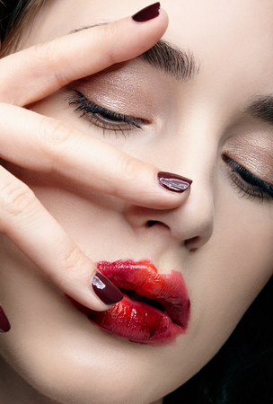 Closeup beauty portrait of young woman with hands near face. Brunette girl with unusual alyapy red female face makeup and eyes closed.