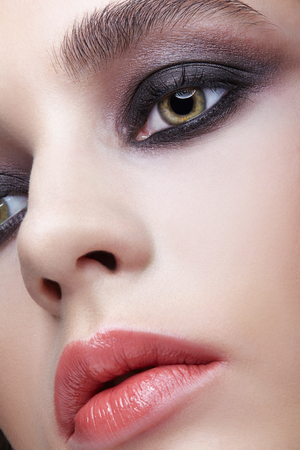 Closeup macro portrait of female face. Woman with unusual evening beauty face makeup . Girl with perfect skin, green pistachio colour eyes and violet - black smoky eyes make-up. Фото со стока
