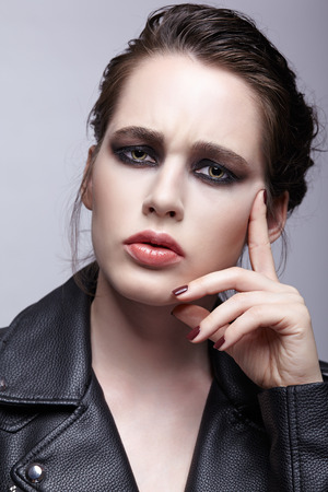 Portrait of female in black leather jacket. Woman with unusual beauty evening makeup. Girl with perfect skin, green pistachio colour eyes and violet - black shadows make-up. Banque d'images