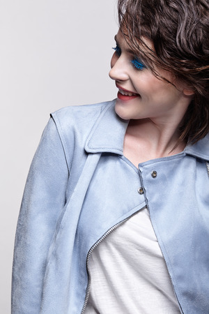 Portrait of smiling female in blue jacket. Woman with unusual beauty makeup and wet hair. Girl with perfect skin, green pistachio colour eyes and blue shadows make-up.