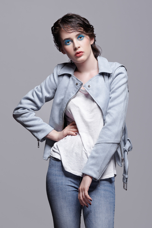 Portrait of female in blue jacket. Woman with unusual beauty makeup and wet hair. Girl with perfect skin, green pistachio colour eyes and blue shadows make-up.